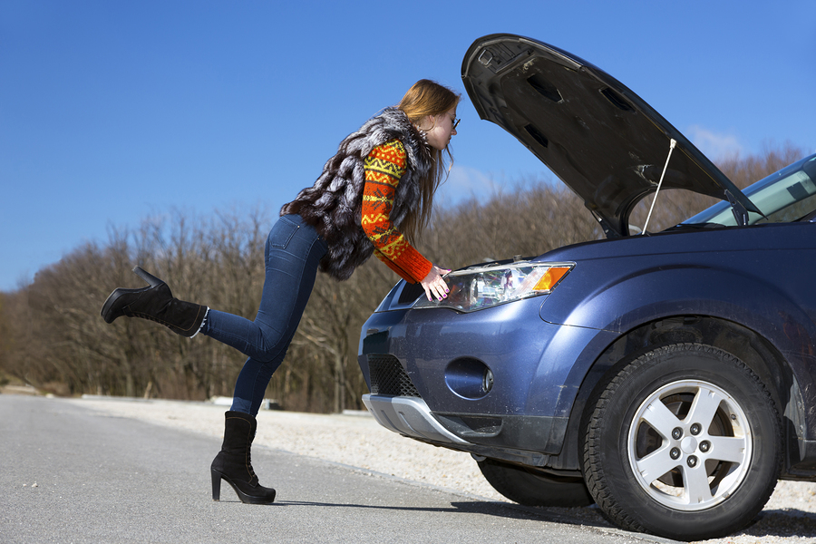 Female driver inspects her car engine